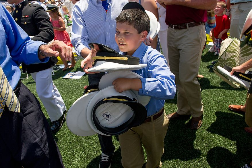 Logan Sullivan, 10, Yuba City, Ca. grabs as many hats as he can following the U.S. Naval Academy's class of 2012 hat toss at the end of their graduation at the Navy-Marine Corps Stadium, Annapolis, Md., Tuesday, May 29, 2012. (Andrew Harnik/The Washington Times)