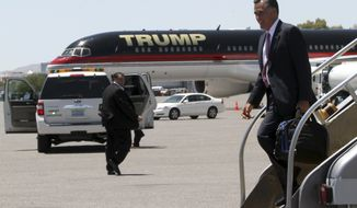 Republican presidential candidate, former Massachusetts Gov. Mitt Romney walks past Donald Trump's airplane as he arrives in Las Vegas, Tuesday, May 29, 2012. (AP Photo/Mary Altaffer)