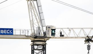 A man who threatened to shoot police officers trying to talk him down from a construction crane sits in the structure's cab 150 feet above the Southern Methodist University campus in Dallas on Monday, May 28, 2012 (AP Photo/Dallas Morning News, David Woo)