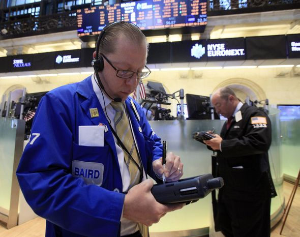 Trader Edward Radziewicz (left) works May 29, 2012, on the floor of the New York Stock Exchange. (Associated Press)