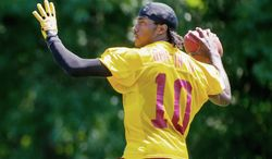 Rookie Robert Griffin III will be firing passes to new Redskins receivers Pierre Garcon and Josh Morgan, both signed as free agents.  (Andrew Harnik/The Washington TImes)
