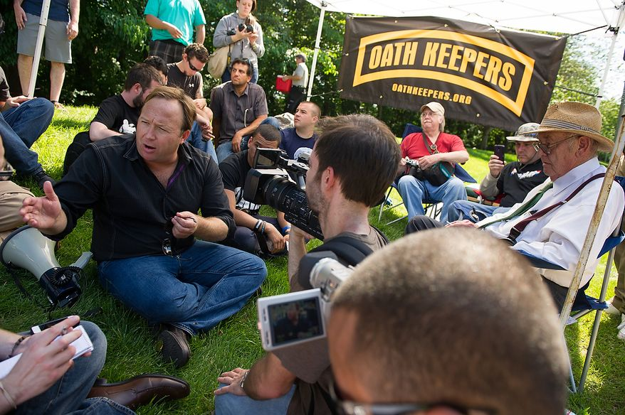 Alex Jones, a radio personality and conspiracy theorist, left, and Jim Tucker, an auther and journalist who has been writing about the Bilderberg Conference since 1975, right, speaks with protesters and members of the media during a demonstration at the entrance to the Marriott Westfields where the annual Bilderberg Conference is being held, Chantilly, Va., Thursday, May 31, 2012. The Bilderberg Conference is an annual meeting of highly influential people in private industry and public office from North America and Western Europe. (Andrew Harnik/The Washington Times)