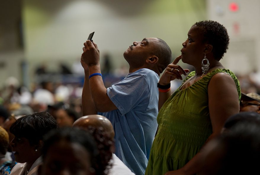 A man and woman in the crowd stand to get a better view of one of the tributes during the memorial service for Chuck Brown Thursday, May 31, 2012 at the Washington Convention Center in Washington, D.C. The event included several musical tributes to the man they call the Godfather of Go Go. (Barbara L. Salisbury/The Washington Times)