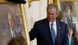 Former President George W. Bush and former first lady Laura Bush, right, unveil their portraits in the East Room of the White House in Washington, Thursday, May 31, 2012. (AP Photo/Carolyn Kaster)