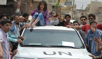 In this citizen journalism image taken on May 29, 2012, and provided by Edlib News Network ENN, a Syrian girl sits atop of a U.N. observers vehicle during a demonstration in Kfarnebel, Idlib province in northern Syria. (Associated Press/Edlib News Network ENN)