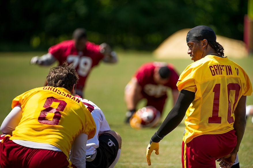 Washington Redskins quarterback Rex Grossman (8), left, and Washington Redskins quarterback Robert Griffin III (10), right, talk as they warm up before an organized team activity at Redskins Park, Ashburn, Va., Thursday, May 31, 2012. (Andrew Harnik/The Washington Times)