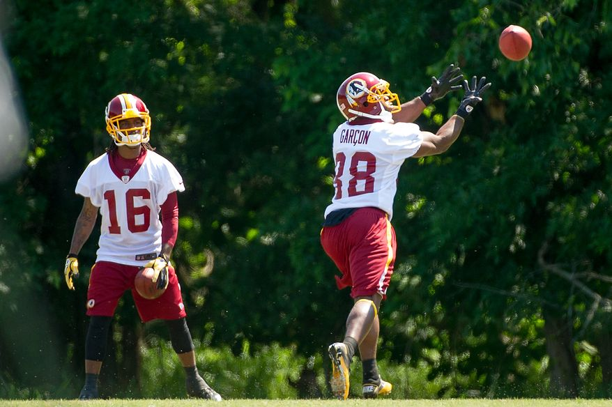 Washington Redskins wide receiver Brandon Banks (16), left, watches as Washington Redskins wide receiver Pierre Garçon (88), right, catches a pass during an organized team activity at Redskins Park, Ashburn, Va., Thursday, May 31, 2012. (Andrew Harnik/The Washington Times)