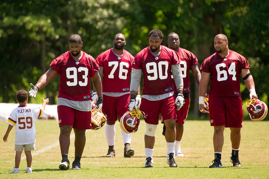 Washington Redskins defensive end Kentwan Balmer (93), second from left, shakes hands with Macaiden Brown, 4, the son of Morocco Brown, Director of Pro Personnel for the Redskins as players leave the field after an organized team activity at Redskins Park, Ashburn, Va., Thursday, May 31, 2012. (Andrew Harnik/The Washington Times)