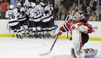 New Jersey Devils' goalie Martin Brodeur gets up from the ice as the Los Angeles Kings celebrate Anze Kopitar's game-winning goal in overtime of Game 1 of the Stanley Cup Final on Wednesday, May 30, 2012 in Newark, N.J. The Kings won 2-1. (AP Photo/Julio Cortez)