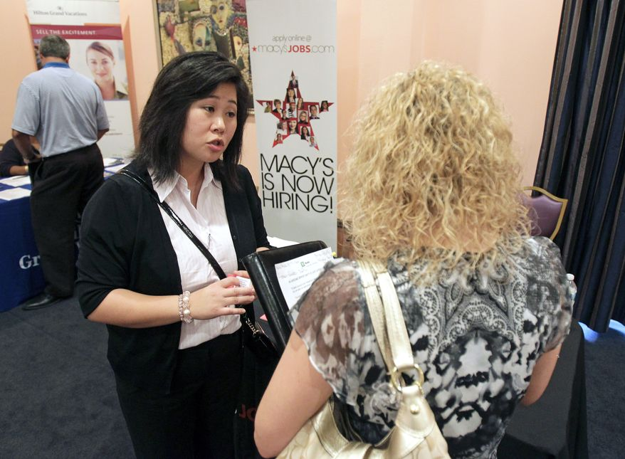 Mi-Ran Park-Wong (left) of Macy's speaks with a job applicant during a career expo sponsored by Jobs Direct USA in Orlando, Fla., on Wednesday, May 30, 2012. (AP Photo/John Raoux)