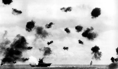 Smoke rises from the USS Yorktown after a Japanese bomber hit the aircraft carrier in the Battle of Midway near the Midway Islands in June 1942 during World War II. Bursts from anti-aircraft fire fill the air. (Associated Press/U.S. Navy)