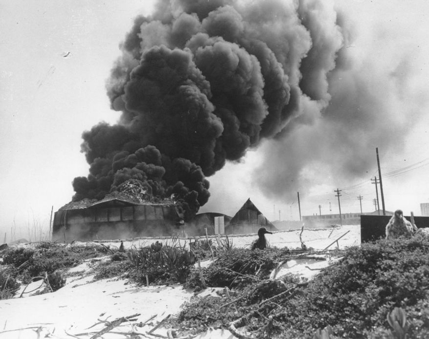 Black smoke rises from a burning U.S oil tank, set afire during a Japanese air raid on Midway Atoll on June 4, 1942. (Associated Press)