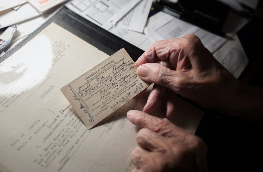 """Retired Rear Adm. Donald """"Mac"""" Showers, 92, shows his 1942 military registration card, or identification card, at his home in Arlington, Va., on November 22, 2011. Showers is one of the remaining survivors that helped lead the effort to break the Japanese code which resulted in a victory at battle of Midway in 1942. (Andrew S. Geraci/The Washington Times)"""