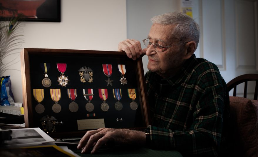 """Retired Rear Adm. Donald """"Mac"""" Showers, 92, looks at medals he received while on active duty during World War II at his home in Arlington, Va. on May 3, 2012. Showers is one of the remaining survivors that helped lead the effort to break the Japanese code which resulted in a victory at battle of Midway in 1942. (Andrew S. Geraci/The Washington Times)"""