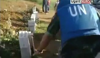 ** FILE ** In this image made from amateur video released by Ugarit News and accessed Saturday, May 5, 2012, a U.N. observer, right, inspects what residents of the town of Taftanaz, Syria, tell him is a mass grave. The Associated Press cannot independently verify the content, date, location or authenticity of this material. (AP Photo/Ugarit News via AP video)