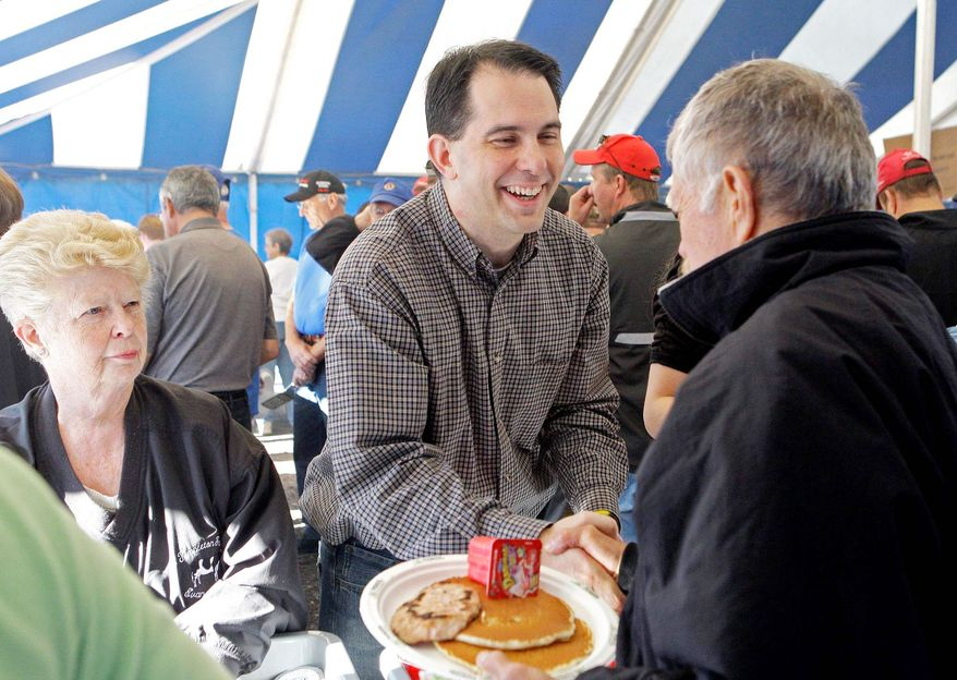 Gov. Scott Walker greets prospective voters at the Rock County Dairy Breakfast in Evansville, Wis., on Saturday, in advance of Tuesday's recall vote. Some political analysts say the outcome of that vote could be a harbinger of how the state will go in November's presidential election. (Associated Press)