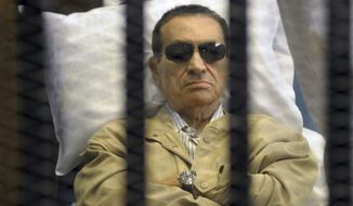 Former Egyptian President Hosni Mubarak lies on a gurney inside a cage in the police academy courthouse in Cairo on Saturday, June 2, 2012. Mubarak was sentenced to life in prison for his role in the killing of protesters during the revolution that forced him from power last year. (AP Photo)