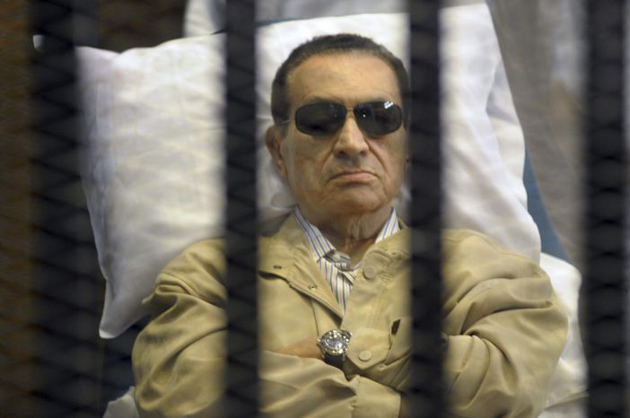 Former Egyptian President Hosni Mubarak lies on a gurney inside a cage in the police academy courthouse in Cairo on Saturday, June 2, 2012. Mubarak was sentenced to life in prison for his role in the killing of pr
