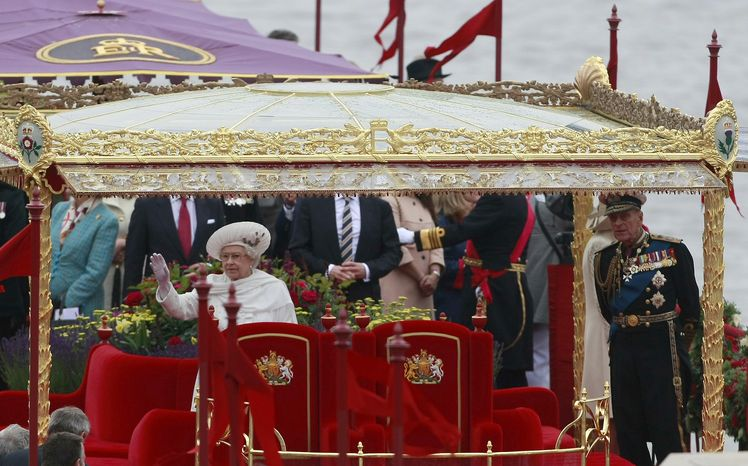 Britain's Queen Elizabeth II and Prince Philip are seen on the Royal Barge as they pass the House of Commons and Big Ben during the Thames Diamond Jubilee River Pageant in London on Sunday, June 3, 2012. (AP Photo/Tim Hales)