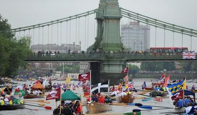 Rowboats gather near the Hammersmith Bridge on the River Thames in London for the Diamond Jubilee river pageant on Sunday, June 3, 2012, to celebrate Queen Elizabeth II's 60-year reign. (AP Photo/Anthony Devlin, Press Association)
