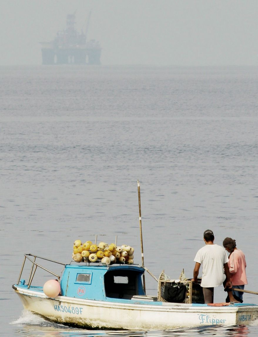 An oil rig in the distance starts exploratory drilling beneath the waters off Cuba's northern coast in January as fishermen work in Havana Bay. On May 18, Spanish company Repsol announced that the exploratory oil well had failed and will be capped and abandoned. (Associated Press)