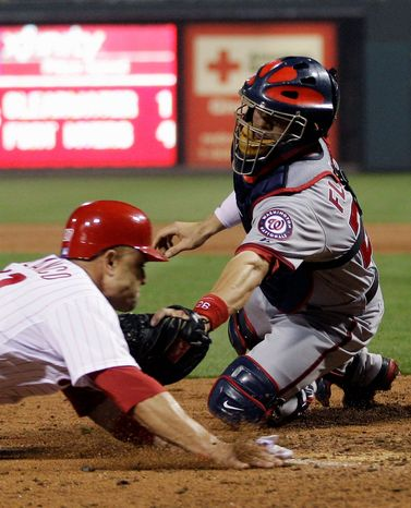 Washington Nationals catcher Jesus Flores, right, tags out Philadelphia Phillies' Placido Polanco at home after Polanco tried to score on a fielder's choice by Phillie