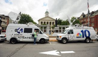 TV trucks line Allegheny Street in front of the Centre County Courthouse in downtown Bellefonte, Pa., the day before jury selection is to begin in the high-profile child-molestation trial of former Penn State assistant football coach Jerry Sandusky. (Centre Daily Times via Associated Press)