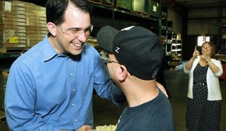 Wisconsin Gov. Scott Walker greets J&D Manufacturing employee Steve Poppe of Eau Claire, Wis., during a visit to the maker of ventilation and other equipment for agriculture and similar commercial applications Monday in Altoona, Wis. (Associated Press)