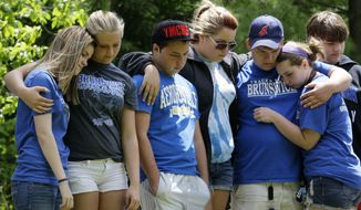 Brunswick High School students console each other June 4, 2012, at a crash site near Brunswick, Ohio. An 18-year-old boy died earlier that day, one day after he was thrown from a car in a crash just hours before his high school graduation. Three other teens were also killed. (Associated Press)