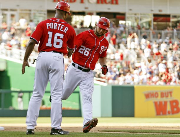 Washington Nationals' Jesus Flores, right, reacts with third base coach Bo Porter while rounding the bases for a solo home run during the fifth inning of a baseball game against the Atlanta Braves
