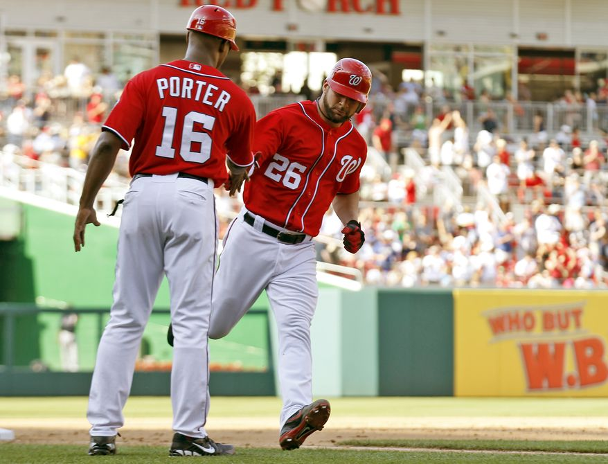Washington Nationals' Jesus Flores, right, reacts with third base coach Bo Porter while rounding the bases for a solo home run during the fifth inning of a baseball game against the Atlanta Braves, Saturday, June 2, 2012, in Washington. The Nationals won 2-0. (AP Photo/Alex Brandon)