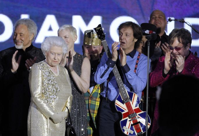 Britain's Queen Elizabeth II, 2nd from left, is joined on stage by performers Sir Tom Jones, Annie Lennox, Sir Paul McCartney and Sir Elton John at the conclusion of the Queen's Jubilee Concert in front of Buckingham Palace, London, Monday, June 4, 2012. The concert is a p