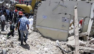 Firefighters and rescuers search for victims at the site of a bomb attack in the central Bab al-Muadham area of Baghdad on Monday, June 4, 2012. (AP Photo/Hadi Mizban)