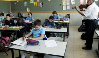 Atif Zarka, 64, a volunteer teacher's assistant, plays the violin for fourth-grade students studying Aramaic in the Arab village of Jish in northern Israel. Mr. Zarka (below) holds the Gospel of Luke written in Aramaic, the language that Jesus spoke, which dominated the region 2,000 years ago. (Associated Press)