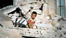 A Syrian boy sits Tuesday amid the rubble of a house in Taftanaz, Syria, that was destroyed during a military operation by the Syrian army in April. Damascus has agreed to allow humanitarian-aid workers from the U.N. and nongovernmental organizations into four Syrian provinces to deliver food, medicine and other supplies. (Associated Press)