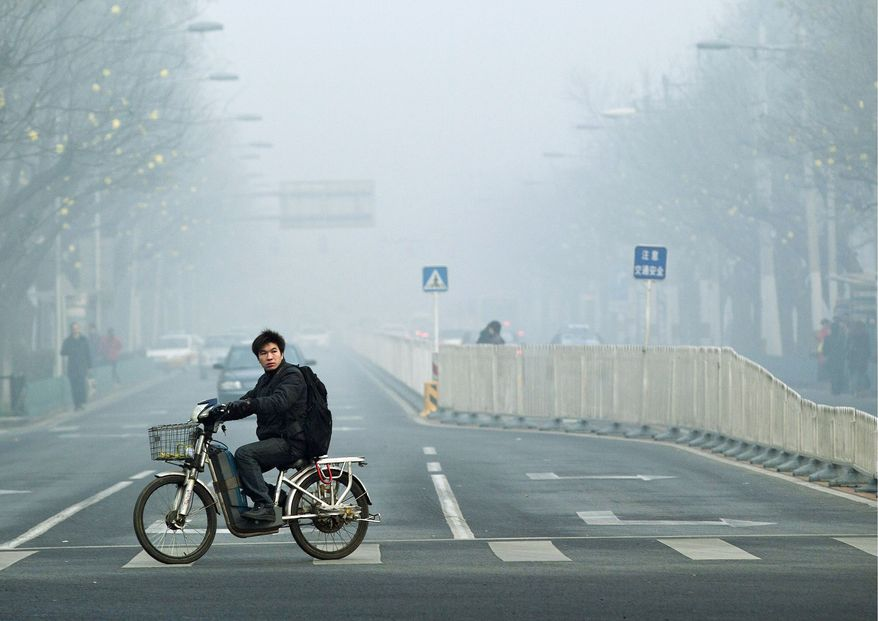** FILE ** In this June 5, 2012, file photo, a man rides an electric bike through the haze in Beijing. (Associated Press)
