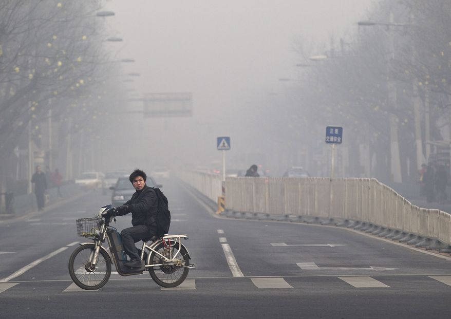 **FILE** A man rides an electric bike in Beijing Jan. 10, 2012, while crossing a street shrouded by haze. (Associated Press)