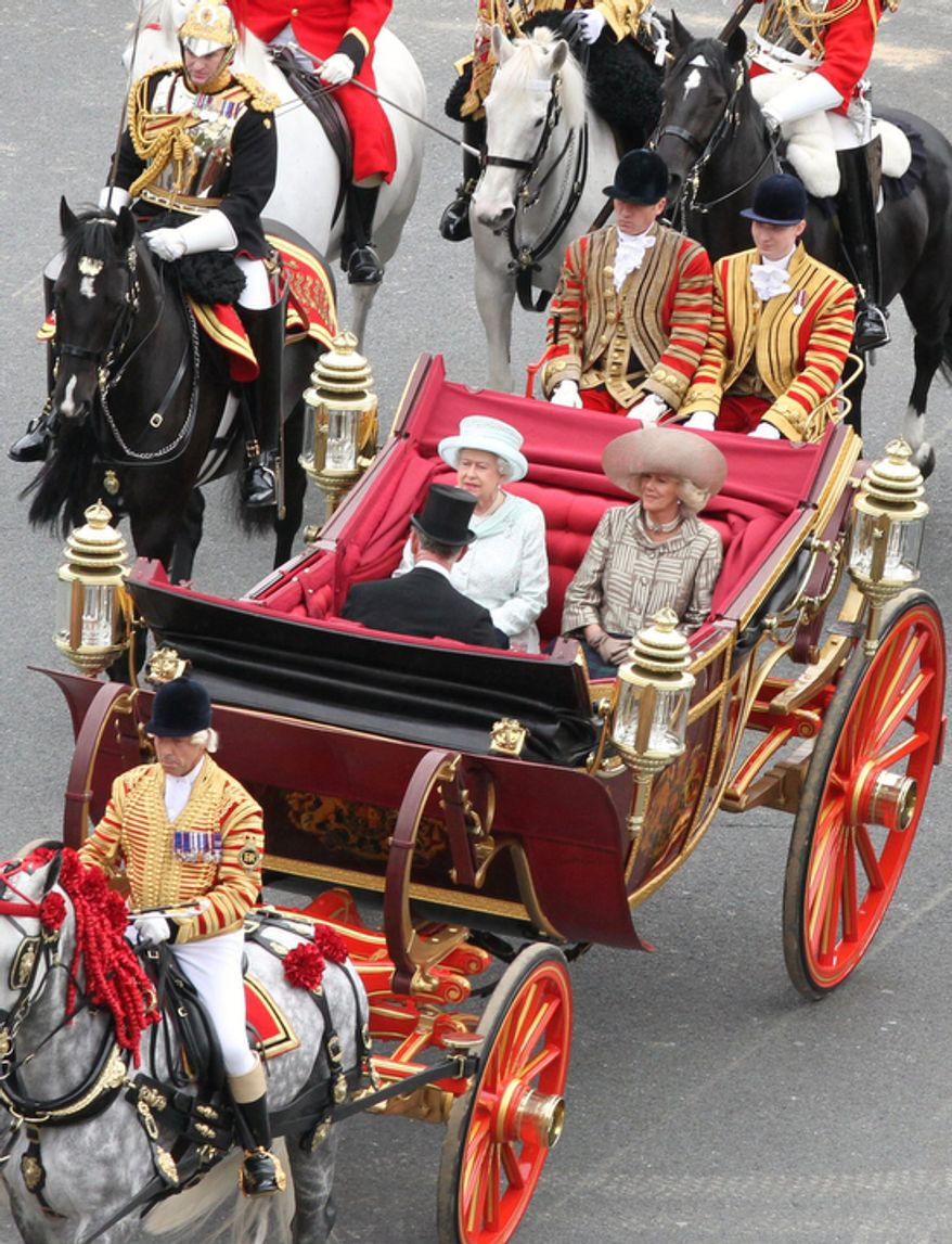 Britain's Queen Elizabeth facing camera left, with Prince Charles and Camilla  Duchess of Cornwall, ride in a carriage as they head for Buckingham Palace in a carriage procession in London. (AP Photo/Elizabeth Dalziel/Pool)