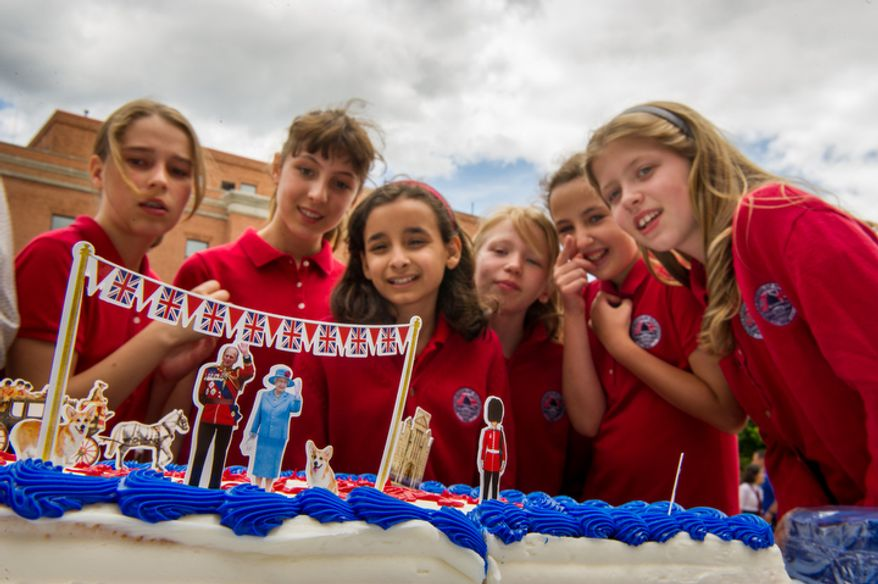 "Students with the British School of Washington check out tiny cut outs of Queen Elizabeth II and Prince Philip, Duke of Edinburgh on a cake during the school's ""Big Picnic Lunch"" in celebration of Queen Elizabeth's Diamond Jubilee. (Andrew Harnik/The Washington Times)"