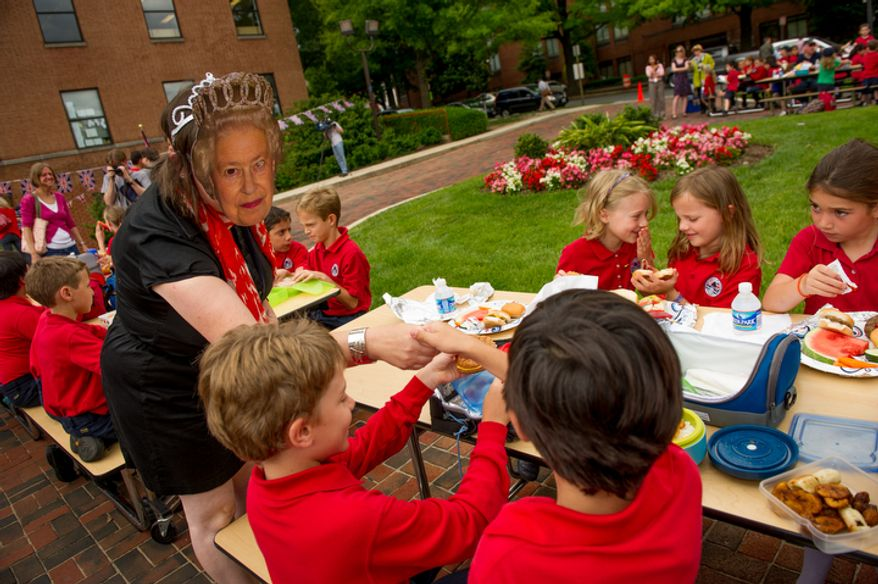 """The British School of Washington's first grade teacher Karen Pena, left, wears a cut out of Queen Elizabeth II on her head as she shakes hands with students during their """"Big Picnic Lunch"""" in celebration of Queen Elizabeth's Diamond Jubilee. (Andrew Harnik/The Washington Times)"""