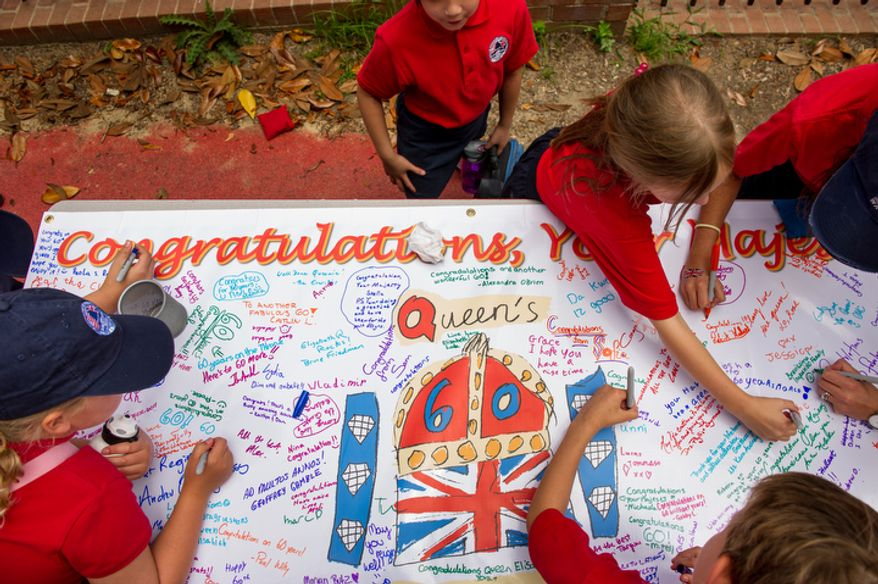 """Students with the British School of Washington sign a banner to Queen Elizabeth II during the school's """"Big Picnic Lunch"""" in celebration of Queen Elizabeth's Diamond Jubilee. (Andrew Harnik/The Washington Times)"""