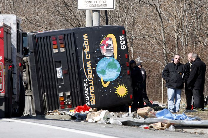 **FILE** Emergency personnel investigate the scene of a March 12, 2011, tour bus crash on Interstate 95 in the Bronx borough of New York. The crash killed 15 passengers. (Associated Press)