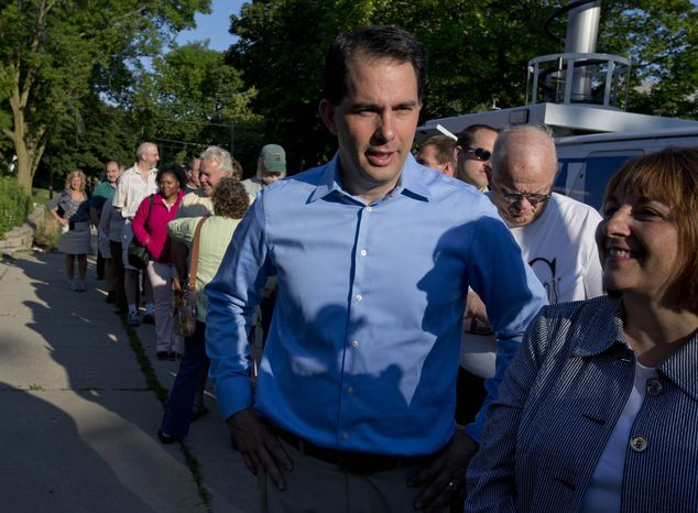 Wisconsin Republican Gov. Scott Walker waits in line to vote Tuesday, June 5, 2012, in Wauwatosa, Wis. Walker faces Democratic challenger Tom Barrett in a special recall ele