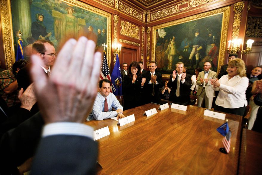 Wisconsin Gov. Scott Walker (seated) gets a standing ovation from his Cabinet and staff at the state Capitol in Madison on Wednesday, a day after he beat Milwaukee Mayor Tom Barrett in a recall election. The outcome cheered Republicans nationwide and caused some optimism for Mitt Romney's prospects in Wisconsin in an expected general election match with President Obama. (Associated Press)