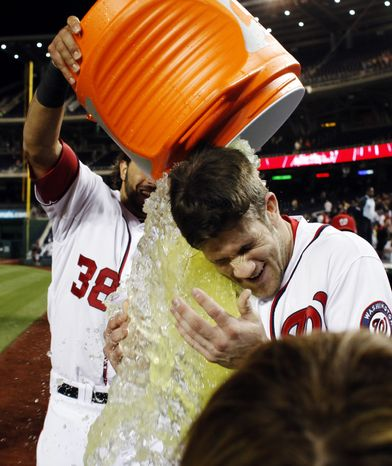 Washington Nationals' Bryce Harper gets dunked by Michael Morse after he hit a walk-off RBI single in the 12th inning against the Mets. (AP Photo/Alex Brandon)