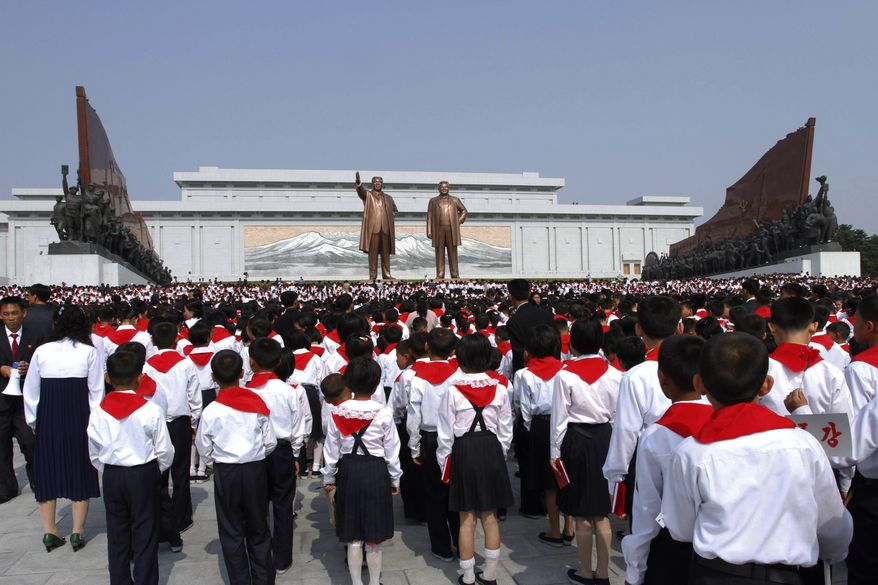 ** FILE ** North Korean students who were selected as delegates to the Korean Children's Union pay their respects in front of bronze statues of late North Korean leaders Kim Il-sung and Kim Jong-il in Pyongyang, North Korea, on Sunday, June 3, 2012. (AP Photo/Jon Chol Jin)