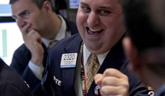 Getco Securities trader Philip Finale (left) and its floor official Peter Giacchi (right) work June 6, 2012, on the floor of the New York Stock Exchange. (Associated Press)