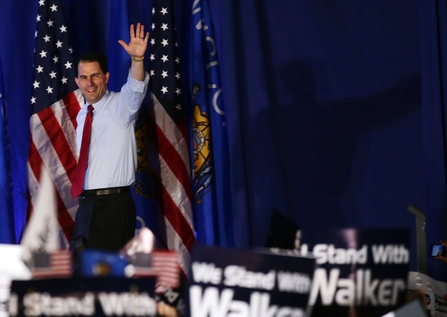 Republican Gov. Scott Walker of Wisconsin waves at his victory party on Tuesday, June 5, 2012, in Waukesha, Wis. Mr. Walker defeated Democratic challenger Tom Barrett in a special recall election. (AP Photo/Morry Gash)