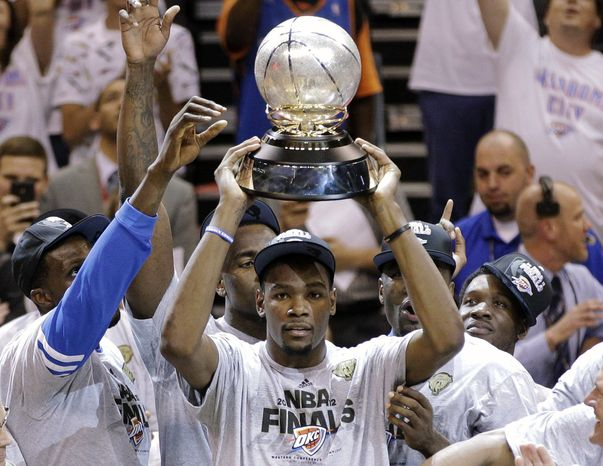 Oklahoma City Thunder's Kevin Durant holds the Western Conference champions trophy after a Game 6 win over the San Antonio Spurs on Wednesday night that helped OKC advance to the NBA finals. (AP Photo/Sue Ogrocki)