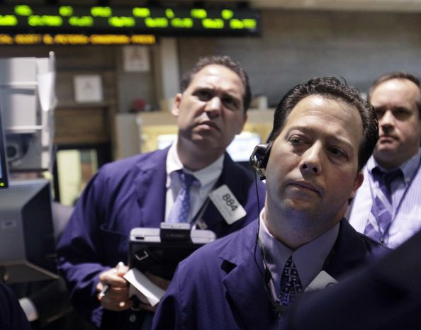 Traders work June 7, 2012, on the floor of the New York Stock Exchange. (Associated Press)